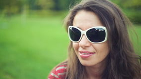 Beautiful woman in sunglasses at the summer park.  stock video