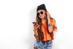 Beautiful woman in sunglasses wearing in black hat and orange T-shirt listening music near white wall, holding a cell Stock Images