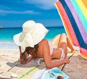 Beautiful woman in sunhat enjoying looking view of beach. royalty free stock photography