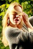 Beautiful woman in the sunny forest, covered her face with hair, Stock Photography