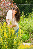 Beautiful woman sunny garden care yellow flowers Royalty Free Stock Photos