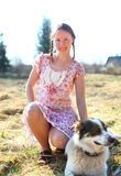 Beautiful woman in a sunshine with a dog Royalty Free Stock Photography