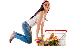 Beautiful woman with a supermarket trolley. In a jump Royalty Free Stock Photos