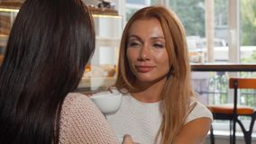 Beautiful woman supporting her best friend, petting her on the shoulder. Young beautiful red haired female talking to her friend at the coffee shop, being stock video footage