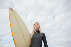 Beautiful woman with surfboard against cloudy sky Stock Images