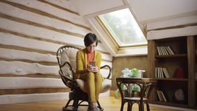 Beautiful woman surfing the Internet on smartphone on attic. Sitting in a chair stock footage