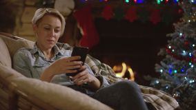 Beautiful woman surfing the Internet on smartphone in New Year night by decorated tree. In front of fireplace sitting in a cosy puffchair stock video