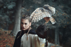 Beautiful woman in surreal forest with an owl. Beautiful lady in surreal forest with an owl . Fantasy and falconry royalty free stock image