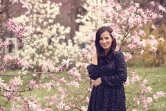 Beautiful woman surrounded by flowers. Smiling Stock Photography