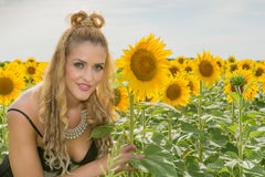 Beautiful woman surrounded by sunflowers Stock Photography