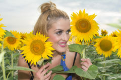 Beautiful woman surrounded by sunflowers Stock Image