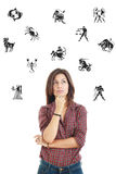 beautiful woman surrounded with zodiac signs thoughtfully looking up with questionable face expression stock image