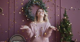 Beautiful woman in sweater blows shiny confetti from her hands to the camera in slow motion, christmas atmosphere stock footage