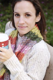Beautiful Woman in sweater holding coffee. A beautiful woman wearing a multi-color scarf, sitting on a bench, and drinking coffee Royalty Free Stock Photo