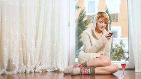 Beautiful woman in sweater sits on floor near window and messaging on phone. Beautiful woman with hood on head in sweater sits on floor near the panoramic window stock video footage