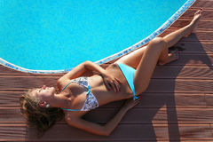 Beautiful woman by swimming pool. Young woman or girl in lightblue bikini by sunny swimming pool in bright sunshine on vacation. Hotel roof, Athens, Greece Royalty Free Stock Images