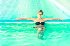 Beautiful woman in swimming pool looking at camera royalty free stock images