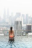Beautiful woman in swimming pool watching the city Stock Photos