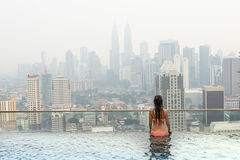 Beautiful woman in swimming pool watching the city Royalty Free Stock Photos