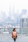 Beautiful woman in swimming pool watching the city Stock Photo