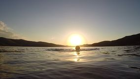 Beautiful woman swimming in the sea at sunset stock footage