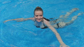 Beautiful woman swimming and smiling in the pool. stock video footage