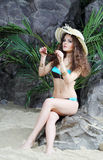 Beautiful woman in swimsuit and hat sits on stone Stock Photography