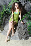 Beautiful woman in swimsuit and jersey sits on stone. Beautiful woman in swimsuit and green jersey sits on stone near gray rocks Stock Photography