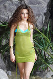 Beautiful woman in swimsuit and jersey walks. Beautiful woman in swimsuit and green jersey walks near gray rocks Royalty Free Stock Photography