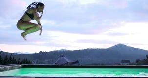 Beautiful woman in swimsuit jumping in swimming pool