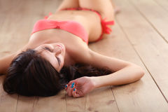 Beautiful woman in a swimsuit is lying on the floor Stock Photos