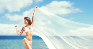 A beautiful woman in a swimsuit posing with a silk blanket on beach Royalty Free Stock Image