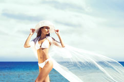 A beautiful woman in a swimsuit posing with a silk blanket on th Royalty Free Stock Photo