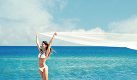 A beautiful woman in a swimsuit posing with a silk blanket on th Royalty Free Stock Images