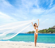 A beautiful woman in a swimsuit posing with a silk blanket Stock Images