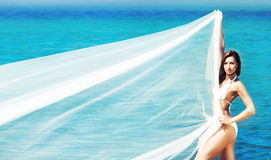 A beautiful woman in a swimsuit posing with a silk blanket Royalty Free Stock Images