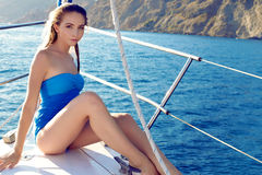 Beautiful woman in swimsuit relaxing on yacht in open sea Stock Images