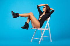 Beautiful woman in swimsuit sitting on a chair. Blue studio bg Royalty Free Stock Photography