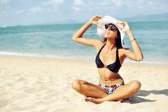 Beautiful woman in a swimsuit sitting on the sand of the beach Royalty Free Stock Image