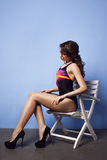 Beautiful woman in swimsuit sitting on white chair near blue wall Stock Photography
