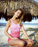 Beautiful woman in a swimsuit under an umbrella Stock Photo