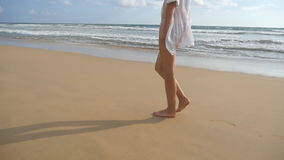 Beautiful woman in swimsuit walking on sea beach barefoot. Young girl going on the ocean shore. Female foot stepping on stock footage