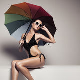 Beautiful woman in swimwear and sunglasses holding umbrella Stock Photos