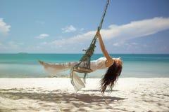 Beautiful woman on a swing near sea Stock Image