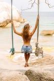 Beautiful woman on swing in tropics. Royalty Free Stock Photos