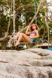 Beautiful woman on swing in tropics. Stock Photos