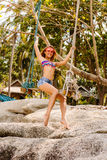 Beautiful woman on swing in tropics. Royalty Free Stock Images