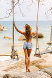 Beautiful woman on swing in tropics. Stock Image
