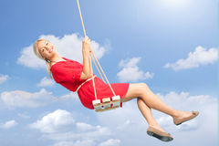 Beautiful woman swinging on a swing outdoors. Beautiful blond woman swinging on a wooden swing outdoors on a beautiful summer day Stock Photo