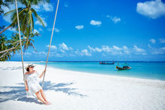 Beautiful woman swinging on a Tropical beach, Koh Phangan island. Thailand. Royalty Free Stock Photos
